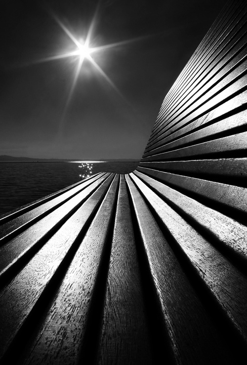 black and white sun over bench at the seaside